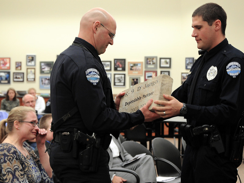 Loveland Police Officer Rob Croner, left, holds back tears Wednesday as he is presented with a memorial stone in honor of his beloved partner, K-9 D'Jango, during a memorial service for the K-9 officer who died last week. Police Officer Steve Marchio, right, hands him the stone as Rob's wife, Christina Croner, far left, wipes away tears.
