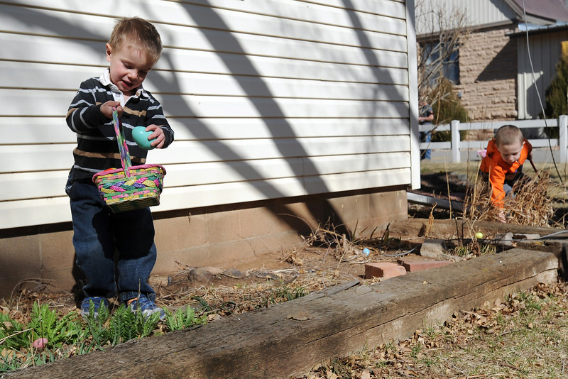 Loveland resident James Mathey, 2, left, plops a plastic Easter egg into his basket after finding it while searching with Chase Miles, 4, right, and other youngsters during an Easter egg hunt Saturday, March 30, 2013 at Buckhorn Presbyterian Church.