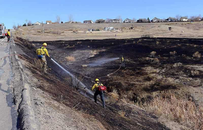 Crews from Loveland Fire Rescue Authority and Poudre fire Authority mop up hots spots during a grass fire at the Cathy Fromme Prairie between Loveland and Fort Collins south of Harmony Road and east of Taft Hill Road on Monday, March 18, 2013.