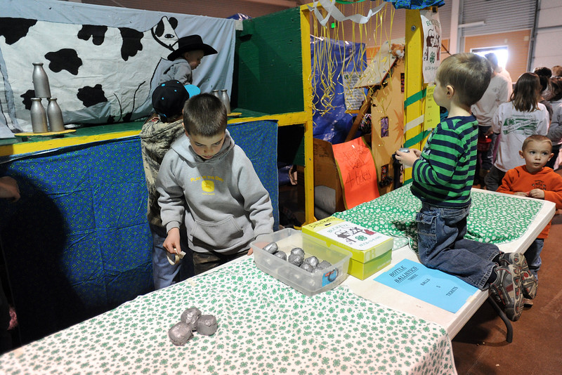 Three-year-old Josiah Lacy kneels on a table as he prepares to play the Bottle Ballistics game being run by Buckeye Buccaneers 4-H Club members, middle from front to back, Zane Paglioti, Wyatt Deer and Daiton Crego during the 4-H Carnival and Craft Show on Saturday, March 23, 2013 in the First National Bank Exhibition Hall at The Ranch.