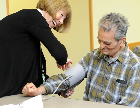 Registered nurse Susan Milligan shares a laugh with Jose Sandoval as she prepares to test his blood pressure at the Chilson Senior Center in Loveland on Monday, Feb. 25, 2013.