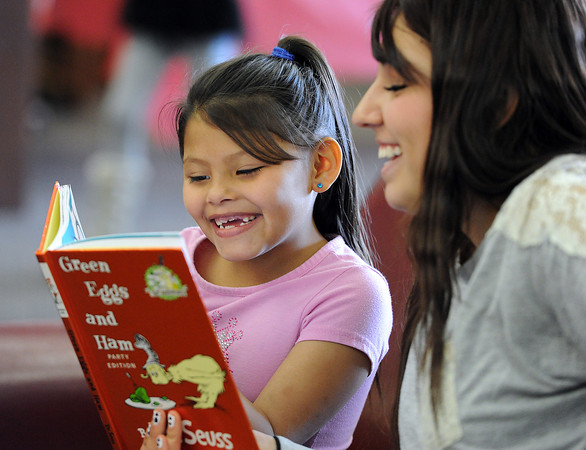"Lincoln Elementary School first-grader Alaina Rodriguez, 7, left, and Loveland High School junior Kacee Martinez, 16, laugh together as they read ""Green Eggs and Ham"" in the library of Loveland High on Friday, March 1, 2013. Students from the two schools paired up to read and play games in honor of Read Across America day."