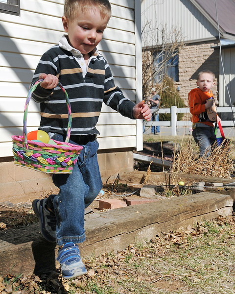 Loveland resident James Mathey, 2, left, dashes off with his basket with his basket while searching for Easter eggs with Chase Miles, 4, right, and other youngsters during an Easter egg hunt Saturday, March 30, 2013 at Buckhorn Presbyterian Church.