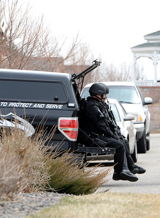 Members of the Loveland Police SWAT Team help with the arrest of a Loveland man on a high stakes warrant at 4070 Buffalo Mountain Drive in east Loveland on Wednesday, March 20, 2013.
