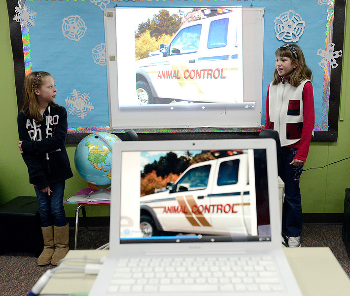 Edmondson Elementary School fifth-graders Aubrey Woodard, 11, left, and Joslyn Richard, 11, right, present what they learned about rabies to a panel at the school in Loveland on Monday, March 11, 2013.