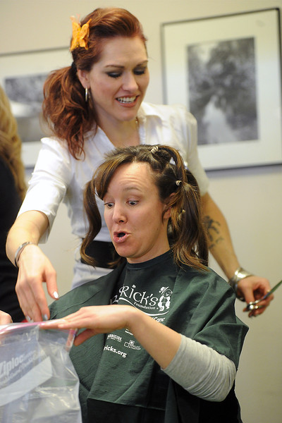 Ponderosa Elementary School health aide Jen Rothfuss, left, reacts after seeing a lock of her hair going into a bag while having her head shaved by stylist Alison Mehls on Saturday at the Thompson School District Administration Building during the Community Resource Fair and St. Baldrick's Event.