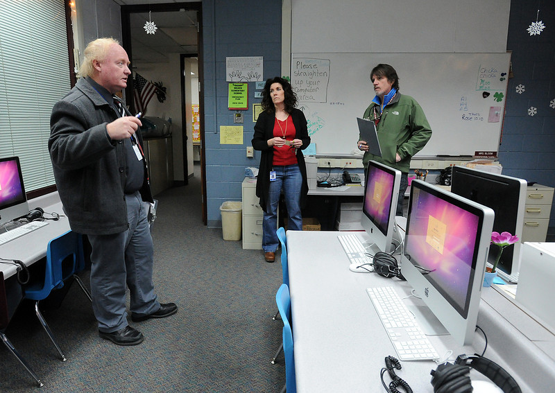 Rick Frei, safety and security manager for the Thomspin School district, left, and Jay Earl, district bond administrator, right, talk with Karen Bloom, technology facilitator at Sarah Milner Elementary School, as they do a security audit of the school in Loveland on Thursday, March 22, 2013.