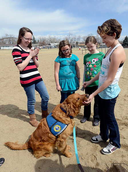 B.F. Kitchen Elementary School students play a game with Copper, the school's therapy dog, during recess at the school in Loveland on Thursday, March 28, 2013. From left are Sabrina Moody, 11, Alena Armstrong, 10, April Conner, 9, and Christina Sible, 10.