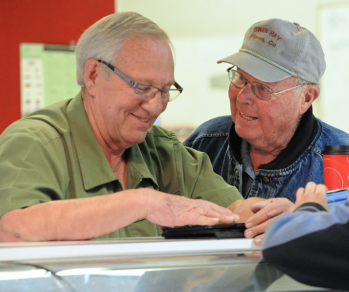 Harry Schmidt, right, the original owner Schmidt's Bakery & Delicatessen, talks with Bill Dickensheet, left, owner of Dickensheet & Associates, the company auctioning off equipment at the bakery in Loveland on Monday, March 25, 2013.