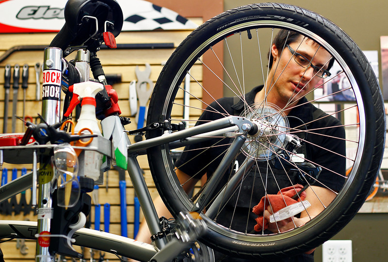 Bike tech Jeremy Rowand demonstrates how to properly lubricate a bike chain Monday afternoon at Lee's Cyclery's Johnstown location.