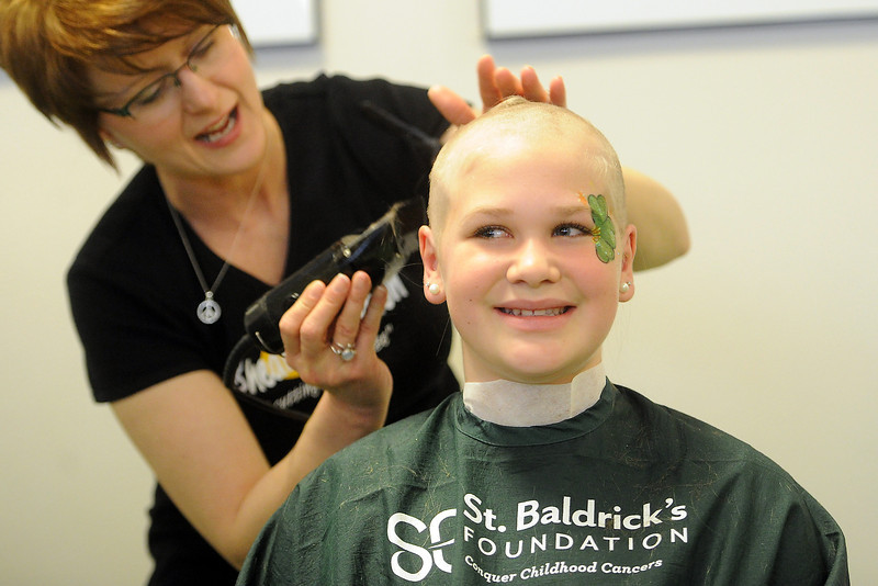 Lucille Erwin Middle School sixth-grader Cassidy Fancher, 12, right, has her head shaved by Shear NV stylist Lori Edsall during the Community Resource Fair and St. Baldrick's Event on Saturday, March 9, 2013 at the Thompson School District Administration Building. Cassidy raised more than $2000 in donations that will toward funding childhood cancer research.