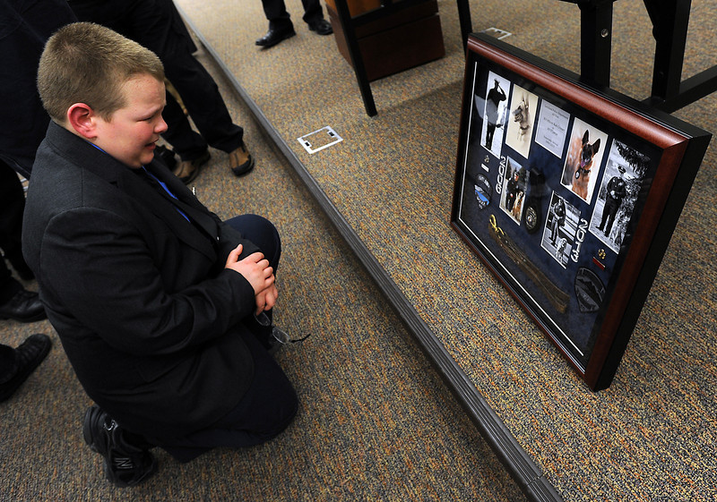 Rob Croner, 10, cries as he looks at a shadow box with photos of D'Jango, his dad,  Officer Rob Croner's K-9 partner, who died last week. The Croner family talked of their love for D'Jango and how he protected them during a memorial service at the Loveland Police Department on Wednesday, March 13, 2013.