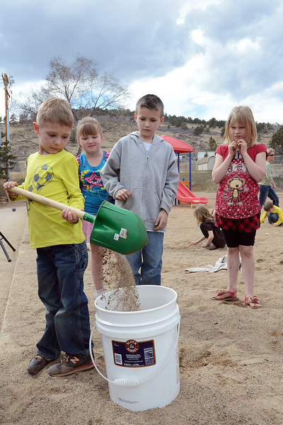 Big Thompson Elementary School first-grader Noah Benjamin, 6, left, empties a shovelful of dirt into a bucket while classmates Shayla Murphy, 6, Wyatt Lindell, 7, and Jaeda Atkins, 7, wait their turn during a groundbreaking event for the school's new playground that's scheduled to open in August.