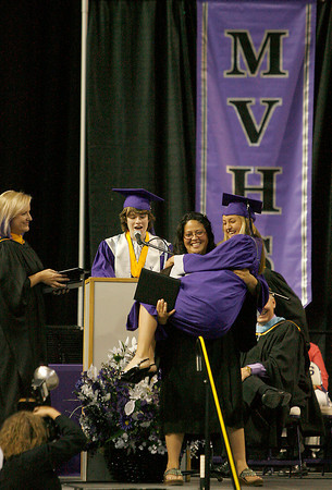 Cortney King jumps into the arms of Mandy Maestas after receiving her diploma Sunday at the Budweiser Events Center.