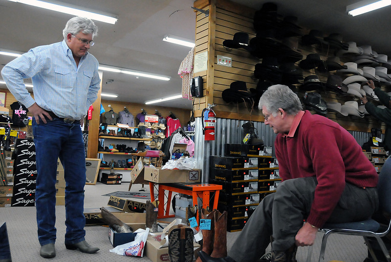 Whiteside's Boots owner John Whiteside, left, lends a hand as Brian Hunt tries on boots on Tuesday, May 11, 2010.