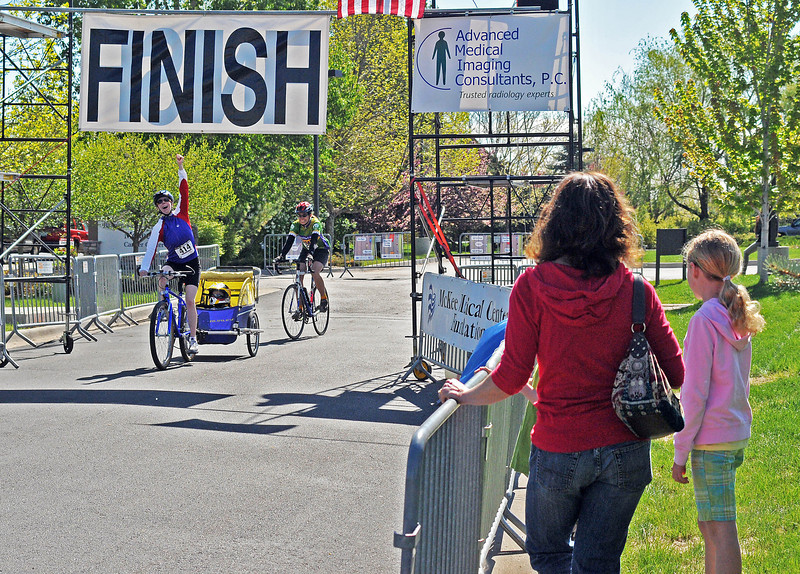 Riders and spectators alike turned out for The Community Classic Bike Tour, Sunday, at the McKee Medical Center. Kayla Christensen, right, waits with her mom, Jennifer Christen, for her dad to cross the finish line.  Meanwhile, Lindsay Gilliland, left, completes her ride with Isaac Gilliland in tow and Erin Axtell, left center, close behind.