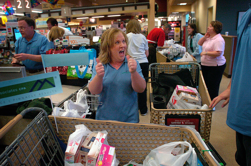 Brooke Hupp of Mueller & Associates celebrates finishing her team's whirlwind shopping spree at the Safeway on West Eisenhower on Thursday morning. Hupp and her teammates, Lou Bush, right, Paul Mueller, left, Ingrid Bush, not in photo, and Teresa Mueller, not in photo, participated in the Reporter-Herald's Shopping Cart Race to kick off the Have a Heart Food Drive. <br /> Photo by Chris Stark