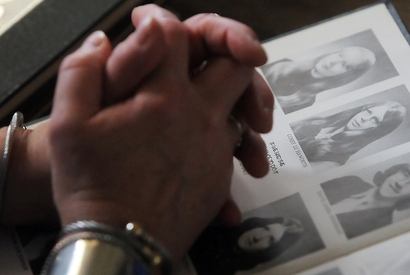 Pat Haworth crosses her hands on a 1974 Berthoud High School yearbook as she talks about her sister, Corby Haworth, who died on July 4, 2008 and is shown at right on the yearbook's page.