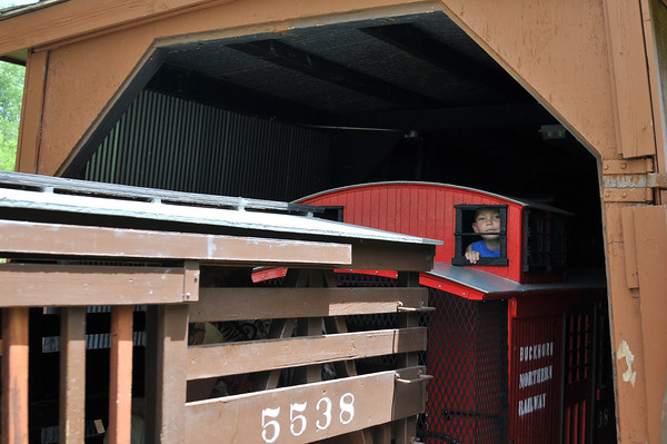 Coen Van Loh, 2, peeps out of the caboose window, Saturday, as The Buckhorn Northern Railroad train emerges from its North Lake Park tunnel during its opening run of the season.