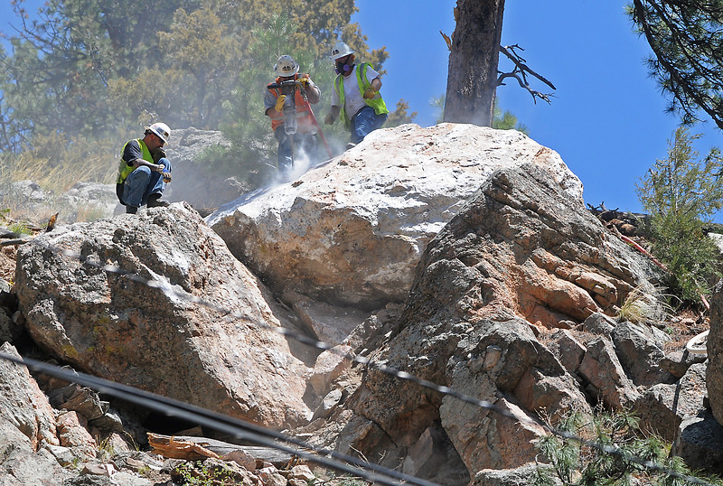 A demolition crew from Arvada-based Yenter Companies drills into a boulder to place exploxives inside as they work to remove loose rock from a hillside adjacent to U.S. 34 just west of Drake on Wednesday, May 26, 2010.