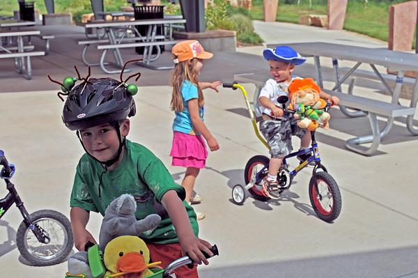 Aidan Jenkins, left, rides his bike around Fairground Park, Friday, while Alexandria Dobson, center, moves to grab the handle on Garrett Jenkins' bike and give him a push.  The group was dressed up for The Annual Pet and Doll Parade sponsored by the Lions Club.