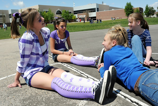 Lucile Erwin Middle School seventh graders, from left to right, Megan Lakatos, 13, Kara Reza, 13, Baylee Ostreim, 13, and Kiley O'neil, 13, hang out together outside the school Friday during their lunch break. Friday was Paint the Town Purple day where students were encouraged to wear purple and also hat day where they could donate one dollar to charity and be able to wear a hat during school. They raised $326 which will be split between the Duck Cancer and TEA Strikes Against Cancer teams for the upcoming Relay for Life fundraiser for cancer research.