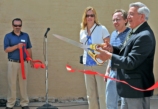 """Mayor Cecil Gutierrez cuts the ribbon in the alley between fourth and fifth streets, Friday, making it as an official part of the Alley Demonstration Project.  """"I envision murals and art in this public space,"""" Gutierrez said.  To his right, from closest to furthest are Kent Solt of Ward 3 City Council, Kelley Savage, landscape architect of Nuszer Kopatz, and Keith Reester, Public Works Director."""