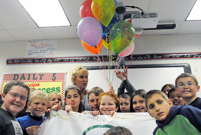 Cottonwood Plains Elementary School teacher Jeanna Dolezal is surrounded by fourth graders in her classroom Wednesday after she was awarded a creativity grant from the Teacher Education Foundation. Dolezal plans to purchase Flip video cameras so her students caqn create video podcast biographies of heroes in their lives.