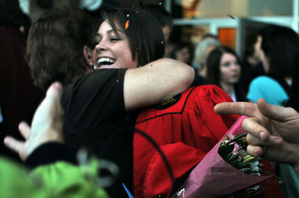 Loveland High School graduate Courtney Flynn celebrates her academic feat with her family as they throw confetti, Sunday, after the graduation ceremony at the Budweiser Event Center.