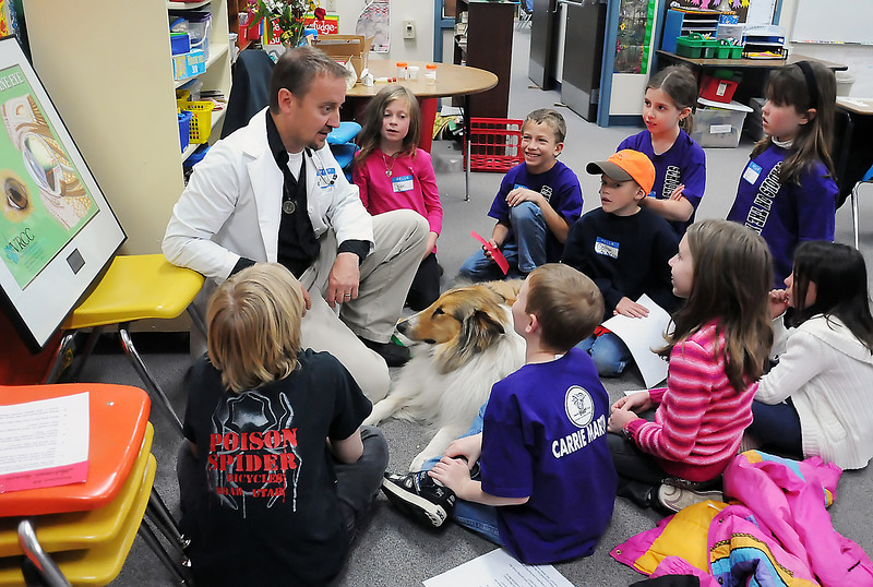 Veterinarian Patrick Owen sits with his dog, Archie, while talking to students at Carrie Martin Elementary School during career day. Many people volunteered to share a little about their professions including an engineer, park ranger, cake decorator, restaurant manager, paleontologist, artist and soldier, among others.