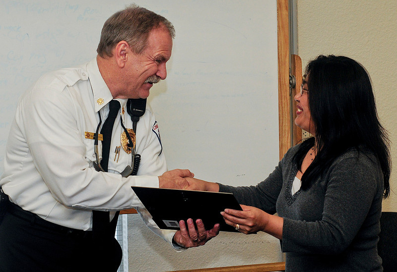 Reporter-Herald/ Chad Spangler<br /> Loveland Fire Department Chief Randy Mirowksi, left, presents a citizens life-saver award to Loveland resident Frances Parsons at Loveland Fire Department on Monday afternoon. Parsons was recognized for discovering a house fire, calling 911 and waking the residents of the home enabling them to escape the blaze.