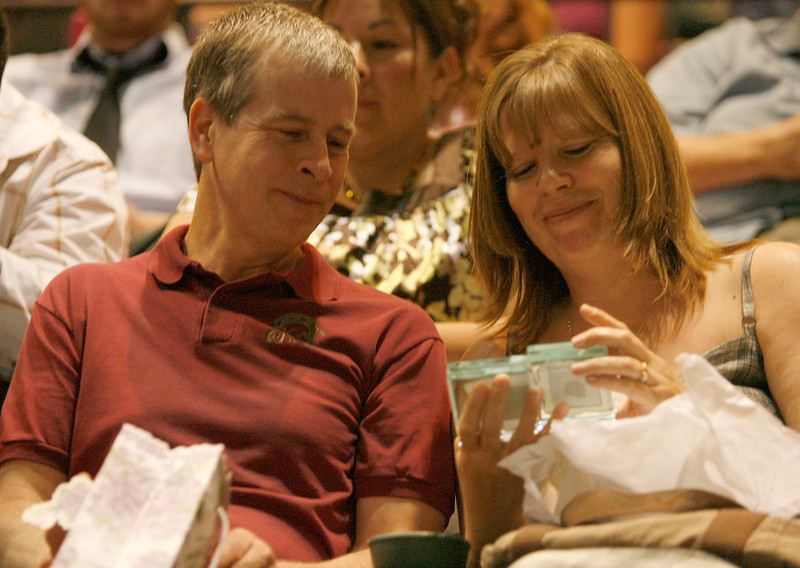 Tim and Heather Michaud look at a gift given to them by their daughter Emily on Sunday during the Mountain View High School commencement ceremony at the Budweiser Events Center.