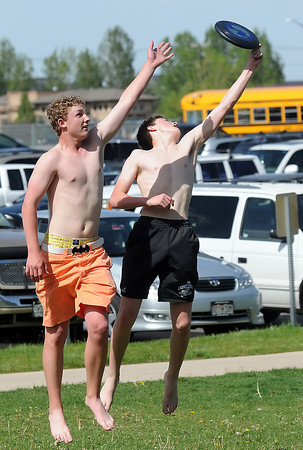 Broomfield residents Nick Reisch, 15, and Cordis Hall, 16, leap into the air to try and grab a flying disc while playing catch with friends Saturday outside the Mountain View Aquatic Center during a break in action for the Class 4A Swimming and Diving Championships.