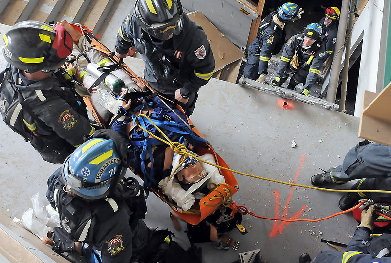 Firefighters and paramedics prepare to lower a training dummy down to other personnel waiting below during an exercise Wednesday at the former Cloverleaf Dog Track as part of the Loveland Special Operations Team training. The 6-day training program included members of Loveland Fire and Rescue, Berthoud Fire Protection District, Union Colony Fire and Rescue and Thompson Valley EMS.