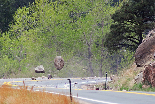 Several large boulders bounce across U.S. 34 west of Drake after being blasted loose with explosives Wednesday afternoon as Colorado Department of Transportation employees and a demolition crew from Arvada-based Yenter Companies work to remove loose rocks from a hillside adjacent to the highway.