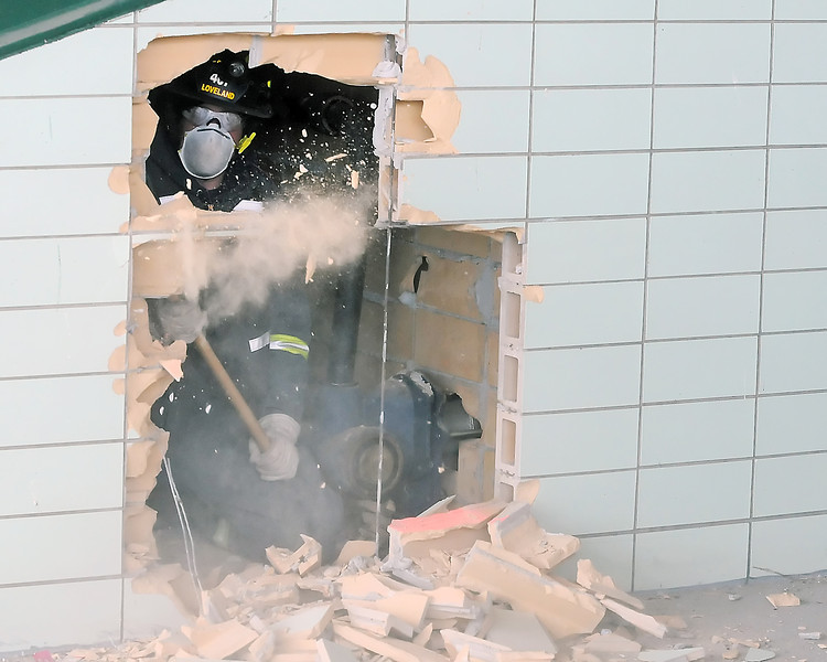 Loveland firefighter Rick Summer uses a sledge hammer to break through a wall at the former Cloverleaf Dog Track during a training exercise Wednesday to find and extricate the victim of a simulated building collapse as part of the Loveland Special Operations Team training.