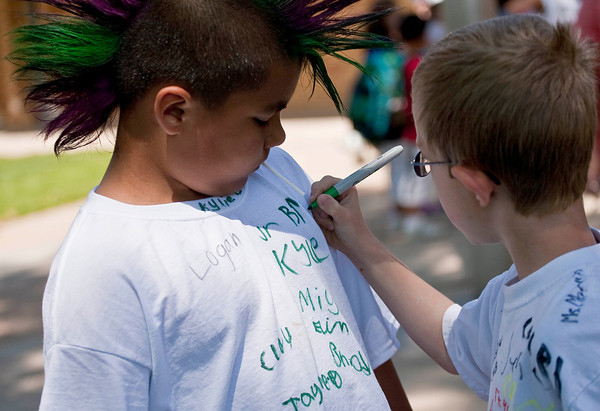Lincoln Elementary School first grade student Ramiro Castillo, left, watches as classmate Bryce Bowman signs his t-shirt outside of the building shortly after classes ended for the year Friday morning.