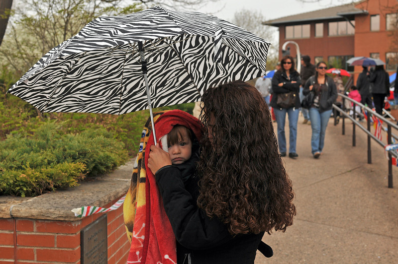 Maria Rubio hurries to bundle and shelter sickly Miguel Ramos, 18 months, from the rain that cut short Sunday's Cinco de Mayo celebration at Foote Lagoon.