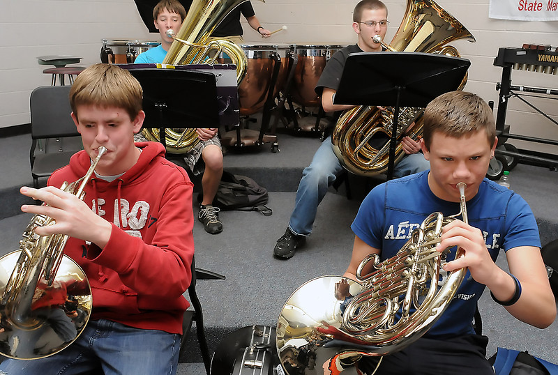 Loveland High School freshman Cort Roberts, 15, left, and junior Tyler Treacy, 17, play their French horns while bandmates Ben Tripam, 17, back left, and Justin Tebbe, 15, play tuba Friday during their wind symphony class.