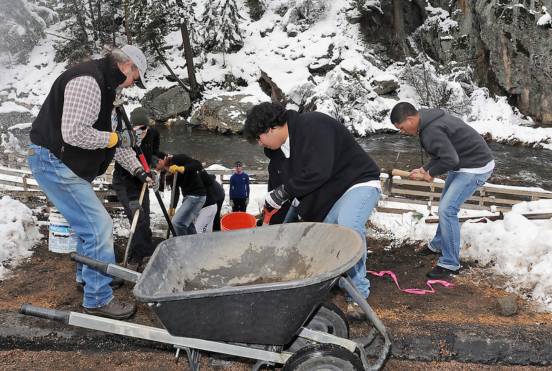 Volunteers, front from left, Dallas Maurer, Alberto Chavez-Hernandez, 17, and J.R. Yama, 15, join others to work on the handicapped-accessible fishing ramp east of Estes Park along the Big Thompson River on Thursday, May 13, 2010.