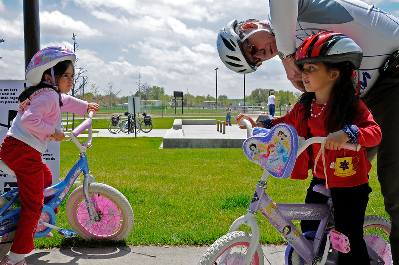 Jerry Buchen gives a new helmet to Maris Moralez, 4, as her sister Avery, 6, rides away on Saturday, May 15, 2010.