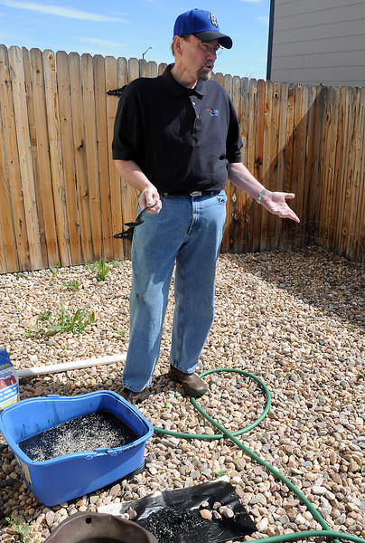 Loveland resident Chuck Black demonstrates a method for removing oil spilled on water that he learned from his uncle by using an absorbant material called UltraSorb that is made for soaking up oil, grease and other liquids.