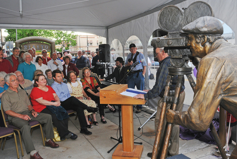 "Roger Clark, right, speaks Wednesday evening outside the Rialto Theater in downtown Loveland during a dedication ceremony for the statue at right titled ""Persistence of Vision"" by, sculptor Pat Kennedy that was dedicated in memory of Phyllis Walbye. Seated from left are Phyllis' husband, George, and children Terry Walbye, Ted Walbye and Kay Walbye Lowman. Seated at right is Susan White, chair of the Loveland Visual Arts Commission."