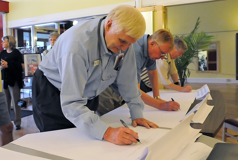 Gary Thomas, left, Tom Ryan and Hal Mansfield jot down their ideas about downtown Loveland during an event Thursday evening at the Cherry Blossom Event Center where city planners and consultants from TST Engineering sought input from the public on a major downtown redevelopment project.