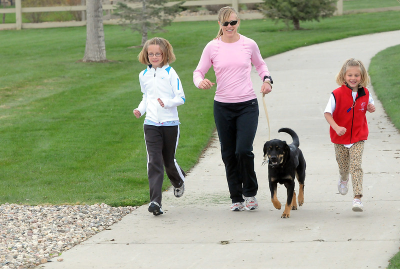 Denise Montague and her daughters, Maisy, 10, left, and Ella, 6, and their dog, Zuko, go for a run together Friday afternoon in northeast Loveland. Maisy and Ella will be participating in the upcoming Healthy Kids Run Series this summer.