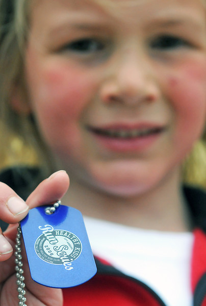 Six-year-old Ella Montague holds up a dogtag that she was given at the completion of a 2008 Healthy Kids Run Series event. After each run children are given a memento of the run which in the past has included hats, clothing, dogtags, wrist bands and backpacks.