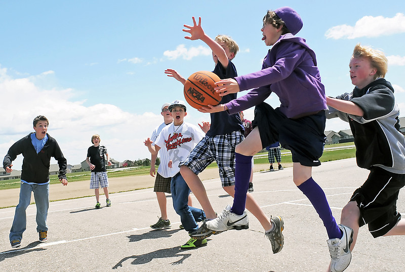 Lucile Erwin Middle School seventh grader Alec Steine, 14, is all decked out in purple hat, jacket and socks as he goes up for a shot while while being guarded by Daniel Williamson, 13, right, and Cole Martin, 13, as they basketball together Friday outside the school after lunch. Friday was Paint the Town Purple day where students were encouraged to wear purple and also hat day where students could donate one dollar to charity and be able to wear a hat in school. They raised $326 which will be divided between the Duck Cancer and TEA Strikes Against Cancer teams for the upcoming Relay for Life fundraiser for cancer research.