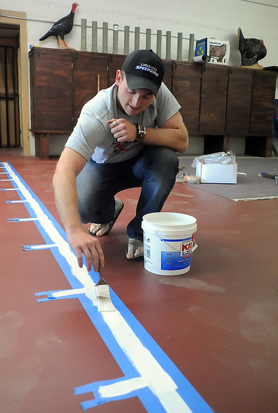 Loveland Archery Exchange pro-shop manager Shane Blindert paints dividing lines Wednesday for shooting stations in the store's 30-yard indoor shooting range. The store opened today and in addition to selling a variety of bows and accessories the store will have shooting leagues for all ages.