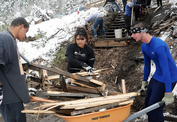 Eagle Rock School students, from left, Q.J. Botefur, 16, Leslie Hernandez, 16, and Lance Burgess, 17, load up wood planks from a fishing ramp along the Big Thompson River east of Estes Park on Thursday, May 13, 2010 as volunteers prepare to install a new ramp at the location.