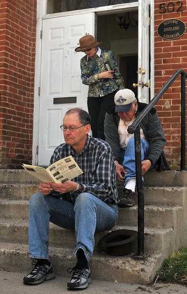 Dennis Merk reads up on Loveland's Histortical Walking Tour out front of the German Evangelical Church on East Seventh Ave, Saturday, while his wife, Sandra Merk, emerges, ready to join him.  Lee Smith puts his shoes back on after exiting.  Shoe removal or covering is required upon entry into the houses.